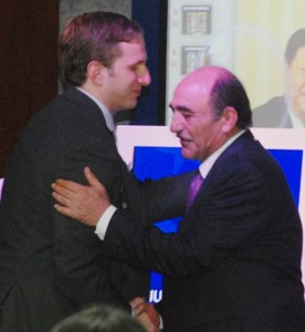 Peter D. Joseph, IIUSA Executive Director, and Harley Seyedin, AmCham South China President, shake hands in front of a packed room of EB-5 industry stakeholders at an IIUSA/AmCham seminar in Guangzhou.